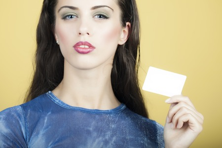 an adult person: Portrait of young pretty sexual brunette girl with red lips in blue holding small white sheet of paper business card standing on yellow background, horizontal picture Stock Photo