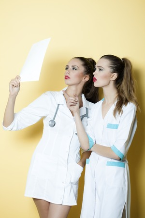 Two young smart serious sexy attractive doctor and nurse in white medical uniform with stethoscope on neck looking in sheet of paper with clinical record standing on yellow background copyspace, vertical picture