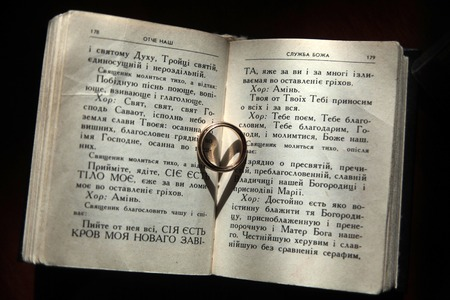 clemency: Reigious prayer book with two wedding golden rings lying and making heart shaped shade on pages with text on black background, horizontal picture
