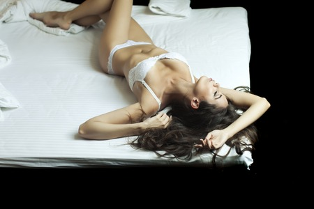nude young: Beautiful passionate sensual young undressed brunette girl with straight body in white lingerie lying in bed, horizontal picture