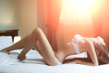 femme se deshabille: Belle sens�e sexy jeune femme brune d�v�tue avec le corps droit en lingerie �rotique blanc couch� dans son lit, horizontale de l'image