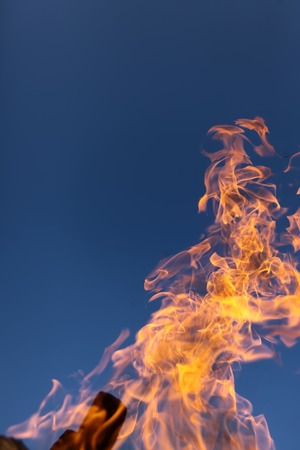 Natural bright hot orange yellow tongues of flame from a bonfire outdoor on clean blue sky background copyspace, vertical picture Stock Photo