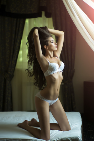 sexy breasts: Attractive tender sexual young undressed brunette woman with straight body in white erotic lingerie sitting on bed in bedroom looking out the window in the morning, vertical picture Stock Photo