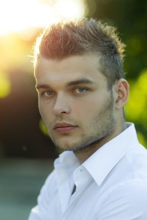 hombres guapos: Retrato del modelo de chico guapo tentadora con la cara hermosa con hoyuelo en la camisa blanca en la puesta del sol en el fondo al aire libre, imagen vertical Foto de archivo
