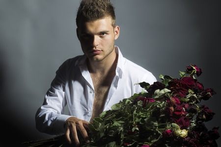 male beauty: Portrait of young sexy handsome macho doy model with beautiful face with dimple in shirt holding bouquet of red rose flowers on grey background, horizontal picture Stock Photo