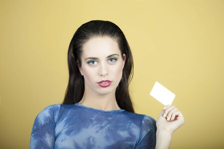area sexy: Portrait of young attractive sexy brunette woman with red lips in blue holding small white sheet of paper business card standing on yellow background, horizontal picture