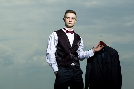 adult sexual: Handsome sexy brutal strong muscular man in formal suit with bow tie holding jacket standing on blue sky background copyspace, horizontal picture Stock Photo