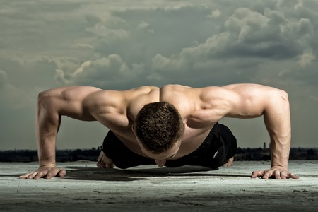 nude yoga: Handsome sexual muscular undressed man bodybuilder training on blue sky background, horizontal picture