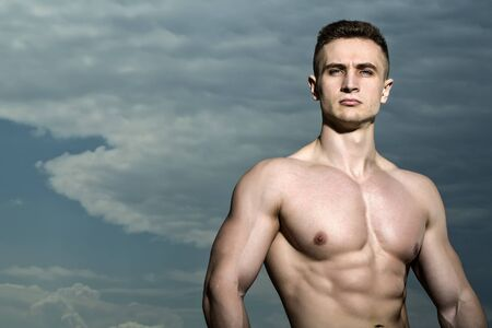 nude male body: Handsome sexy muscular undressed strong man bodybuilder standing on blue sky background copyspace, horizontal picture Stock Photo