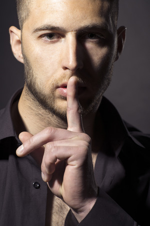 Portrait of sexy handsome unshaven man in black shirt making silence gesture, vertical photo Stockfoto