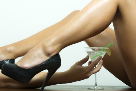 sexy naked girl: Straight naked sexy female legs in black leather shoes on high heels and hand holding cocktail with lime in glass on white background, horizontal picture