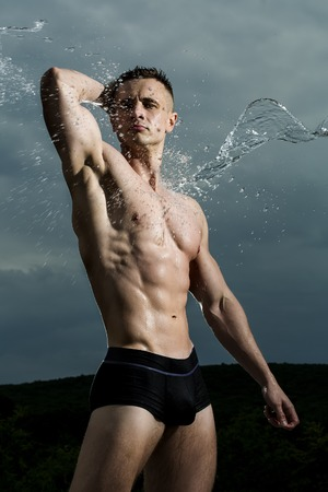 naked male body: Beautiful sexy muscular stripped strong guy bodybuilder in water splashes standing on blue sky background, vertical picture Stock Photo