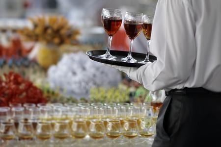 コニャックやブランデー ビュッフェ テーブル、画像の水平方向の近くの黄色のハード飲料のワイングラスを持つトレイを提供して正式な黒と白の服