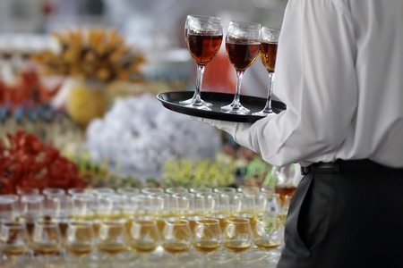 Back view of elegant waiter in formal black and white clothes with serving tray with wine glasses of amber hard beverage of cognac or brandy near full buffet table, horizontal picture