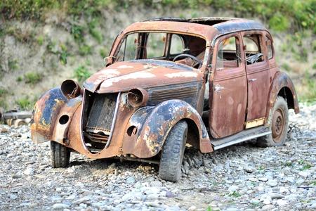 oxidado: Antiguo oxidado edad roto depreció coche retro de pie en el suelo de grava al aire libre, horizontal de la imagen Foto de archivo