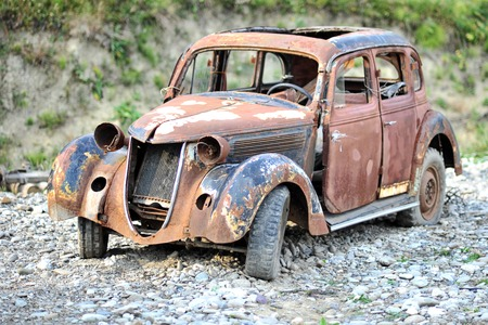 Old aged rusty broken depreciated retro car standing on gravel ground outdoor, horizontal picture