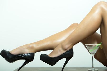 mujer desnuda: Delgadas piernas de mujer sexy desnuda en zapatos de cuero negro en tacones altos y cóctel con cal en vidrio en el fondo blanco, cuadro horizontal