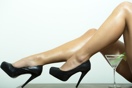 donna completamente nuda: Slim nude sexy gambe femminili in scarpe di cuoio nero su tacchi alti e cocktail con calce in vetro su sfondo bianco, immagine orizzontale
