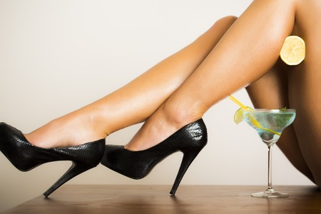 humor: Alluring bare sexy female legs in black leather shoes on high heels with half fresh juicy orange and blue cocktail with green lime in glass on white background, horizontal picture Stock Photo
