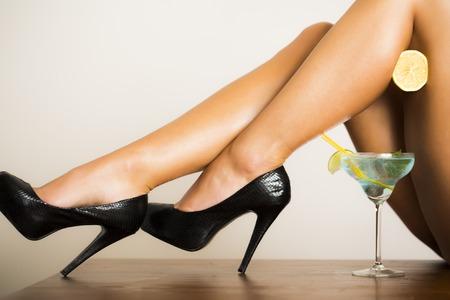 copa martini: Alluring desnudas piernas femeninas atractivas en zapatos de cuero negro en tacones altos con media naranja jugosa fresca y azul cóctel con verde limón en vidrio en el fondo blanco, cuadro horizontal Foto de archivo