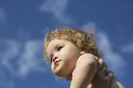 ni�os jugando: Poco ni�o juguet�n hermosa rubia con el soleado d�a al aire libre pelo rizado sobre fondo azul cielo, cuadro horizontal