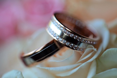 Pair of golden wedding rings with diamonds on bouquet of fresh flowers of pink and white roses closeup, horizontal picture Banque d'images