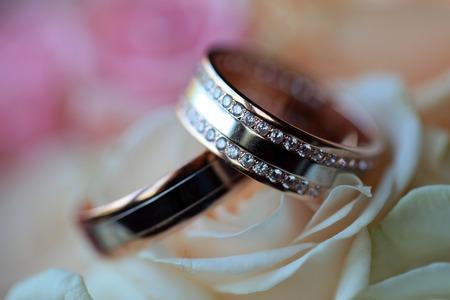 mujer con rosas: Par de anillos de bodas de oro con diamantes en ramo de flores frescas de color rosa y rosas blancas primer, cuadro horizontal