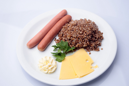 crumbly: Tasty boiled sausages with crumbly buckwheat cheese and sauce decorated with parsley on plate isolated on white, horizontal picture Stock Photo