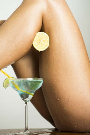 erotical: Beautiful sexual female legs with half fresh juicy orange and blue cocktail with green lime in glass on white background, vertical picture Stock Photo