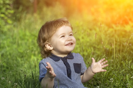Little cute happy smiling baby boy sitting in field on fresh green grass sunny day, horizontal picture