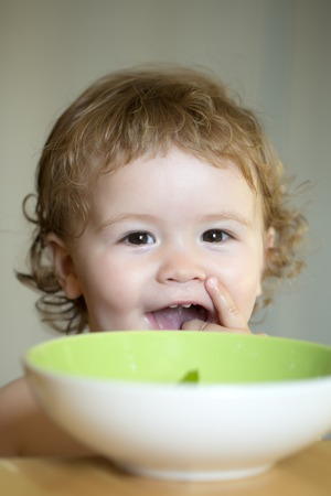 blonde curly hair: Portrait of smiling sweet little boy with blonde curly hair and round cheecks eating from green plate with hand closeup, vertical picture