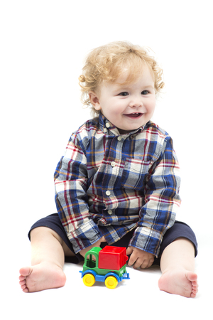 children hands: Funny curly smiling baby boy playing with colored toy car isolated on white background, vertical photo