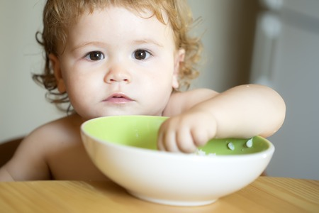 Portrait of interesting small pretty baby boy with blonde curly hair and round cheecks eating from green plate with hand closeup, horizontal picture