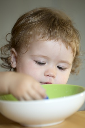 blonde curly hair: Portrait of independent sweet baby boy with blonde curly hair and round cheecks eating from green plate with hand closeup, vertical picture