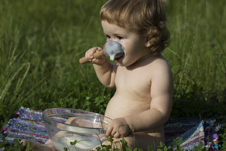 Small pretty male child with curly hair sitting in lawn on green grass eating cream of wheat from glass plate with spoon sunny day, horizontal picture Stock Photo