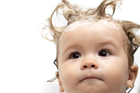 Portrait of little curious attractive male child with wet hair in bathroom looking away on white background closeup, horizontal picture