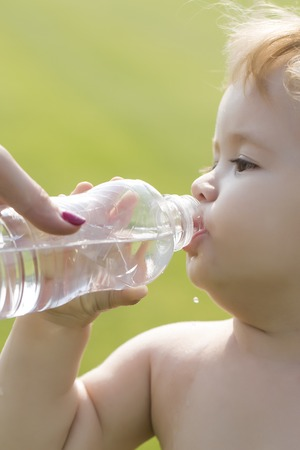 teteros: Closeup of little male child with blonde curly hair round cheeks and cute face drinking water from plastic bottle from hand of mother sunny day outdoor on green grass background, vertical picture