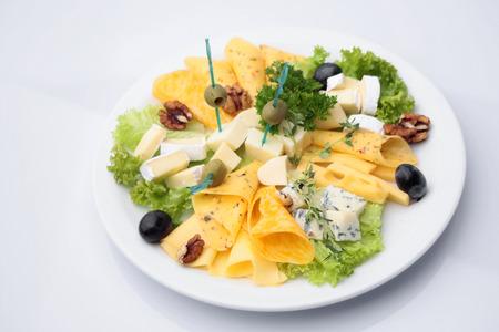 queso: Mezclado plato de queso cena de diferentes variedades de queso decorado con aceitunas nueces perejil lechuga aislado en blanco, cuadro horizontal Foto de archivo