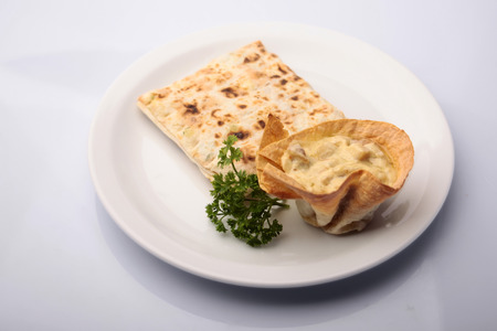 pita bread: Warm tasty pita bread filled with bacon mushrooms and melted cheese with pita folded square decorated parsley on plate isolated on white, horizontal picture