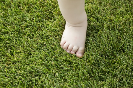 One tiny little bare baby foot of small child with soft skin making step on fresh green lush grass outdoor on natural background closeup, horizontal picture