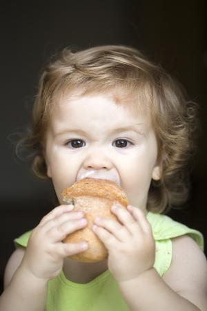 comiendo pan: Hungry pequeño bebé hermoso con el pelo rizado rubio sostiene y que come fresca rollo sabroso pan en backdroung negro, imagen vertical