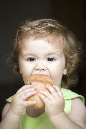 cute baby boy: Hungry small beautiful baby boy with blonde curly hair holding and eating fresh tasty bread roll on black backdroung, vertical picture