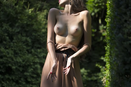 naked statue: Slim beautiful female body of a young half dressed woman with naked chest and soft skin standing in garden among green bushes on sunny day, horizontal picture Stock Photo