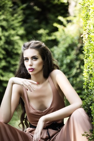 decollete: Portrait of beautiful sexy young woman with bright makeup and long curly brunette hair with deep decollete sitting in green garden with lush plants sunny day outdoor, vertical picture