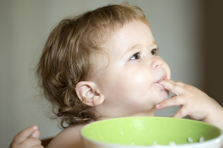 toddler boy: Portrait of funny small pretty baby boy with blonde curly hair and round cheecks eating from green plate with hand closeup, horizontal picture