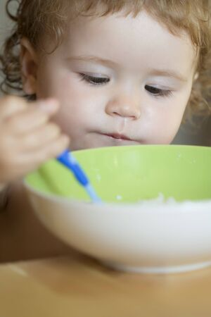 blonde curly hair: Portrait of serious small male child with blonde curly hair and round cheecks eating from green plate with spoon closeup, vertical picture Stock Photo