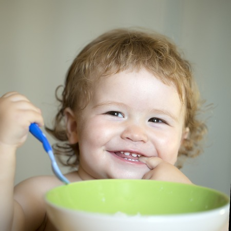blonde curly hair: Portrait of funny little smiling boy with blonde curly hair and round cheecks eating from green plate holding spoon closeup, square picture