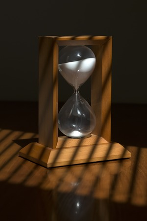 hour glass: Old fashioned retro wooden hour glass clock with white sand standing on table top with jalousie shadow from sun through window, vertical picture Stock Photo