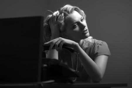 underlay: Overworked pretty secretary woman sitting at office table underlaying in blouse holding phone receiver on bare wall background black and white, horizontal picture