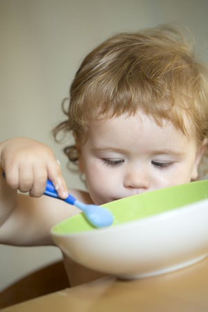blonde curly hair: Portrait of serious little cute male kid with blonde curly hair and round cheecks eating from green plate with spoon closeup, vertical picture Stock Photo